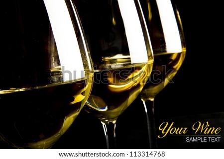 three glasses of white wine on black background