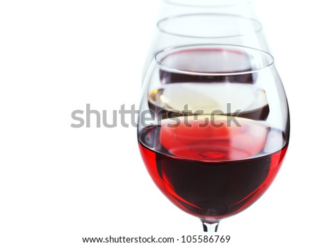 Three glasses of wine stand in a row, over white with copy space