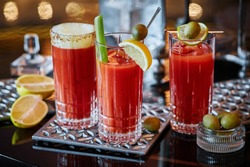 Three glasses with a Bloody Mary cocktail decorated with olives, celery and sliced lemons on metal coasters on a glossy tabletop, three different modern Bloody Mary cocktail recipes