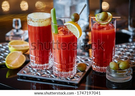 Photo of  Three glasses with a Bloody Mary cocktail decorated with olives, celery and sliced lemons on metal coasters on a glossy tabletop, three different modern Bloody Mary cocktail recipes