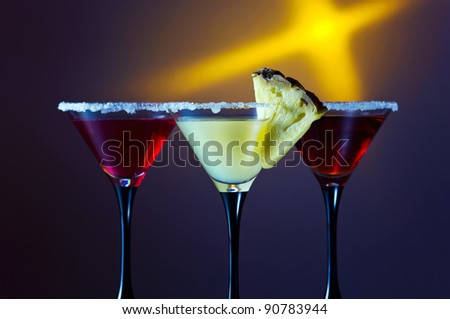 Three glasses with a cocktail on a dark background.