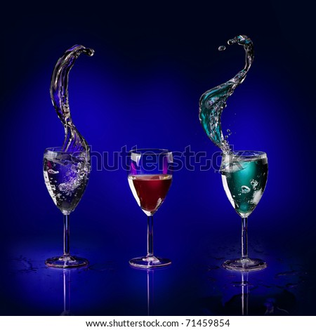 three glasses with colored liquid splashing on a deep blue background