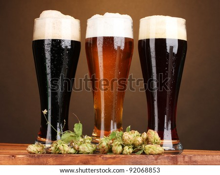 three glasses with different beers and hop on wooden table on brown background