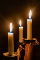Three glowing candles on wooden candlestick, with dark background.