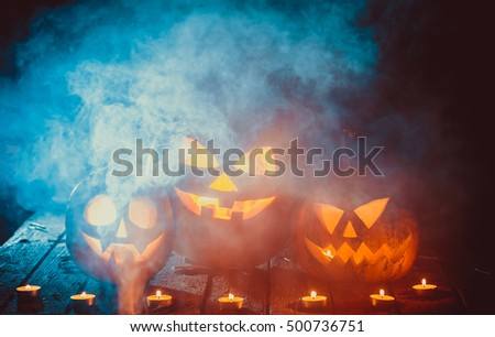Three glowing halloween pumpkins symbolizing the head of old Jack, with smoke on wooden background. Soft focus. Shallow DOF #500736751