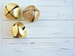 Three Gold Bells on a rustic white wooden background/Three Gold Bells/Christmas Bells Gold