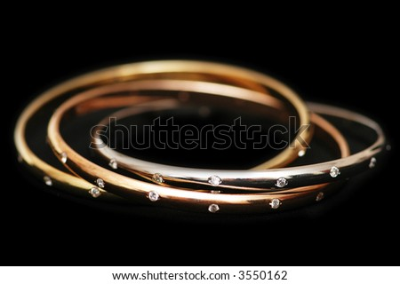 Three gold bracelets isolated on the white - stock photo