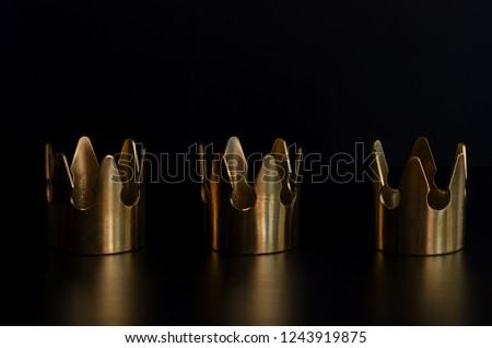 Three gold crowns on black background for Tres Reyes Magos  or Three Wise Men concept background.