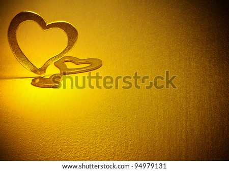 Three gold hearts on a gold background. - stock photo