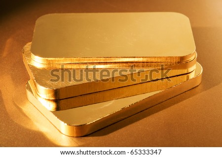 three gold ingots on a golden background. shallow depth of field.