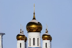 Three golden domes of the church against the background of a bright blue sky. Sunbeams illuminate the golden domes of the church