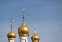 Three golden domes with a crosses of the Orthodox Church against the blue sky. Christian temple, faith concept