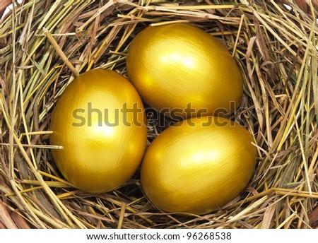 Three golden eggs in the hay nest