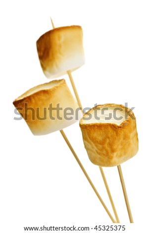 Three golden toasted marshmallows on wooden skewers