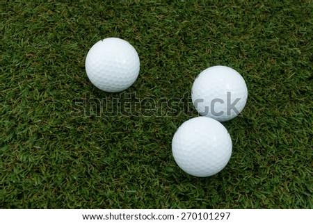 Three Golf ball  on the grass ground.