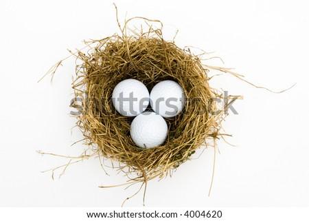 three golf balls in a nest