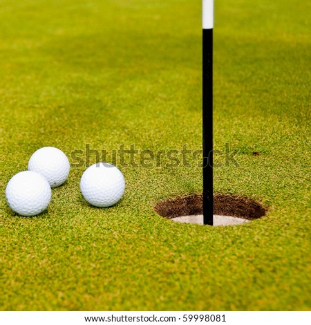 Three golf balls on green with a hole. Shallow depth of field. Focus on the hole and the closest balls.