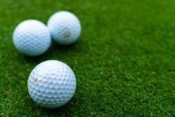 Three golf balls on the green