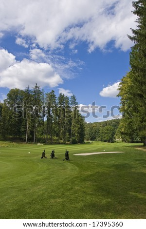 three golf trolleys standing on fairway of a beautiful golf course with dramatic summer sky