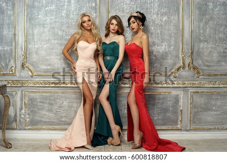 Stock Photo Three gorgeous stunning girls in mermaid evening dresses standing and posing in luxury interior. Brunette, blonde and red hair young elegant woman.