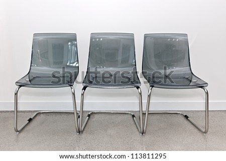 Three gray transparent plastic and metal chairs in a row