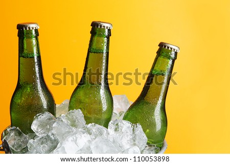 Three Green Beer Bottles in Ice Bucket with Condensation