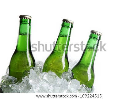 Three Green Beer Bottles in Ice Bucket with Condensation isolated on white