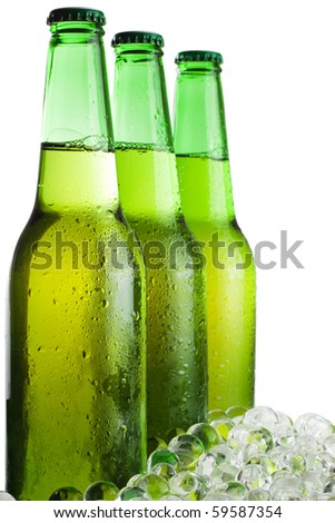 three green beer bottles with ice isolated over white background