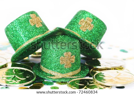 three green glitter hats with gold shamrocks on them with gold coins and confetti for St. Patrick's Day - stock photo