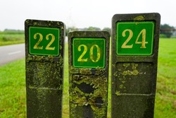 Three green number shields at the road. The concrete posts are covered with lichen.