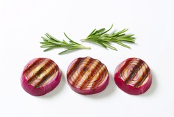 three grilled slices of red onion accompanied with sprig of thyme
