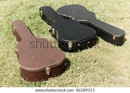 Three guitar cases lying on the ground