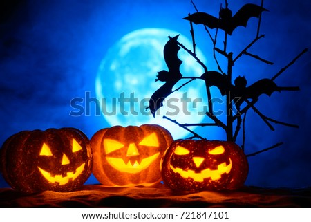 Three Halloween pumpkins and bats on a tree, the full moon in the fog #721847101