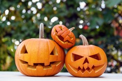 Three Halloween pumpkins or jack-o-lantern at home terrace. Decoration and holidays concept