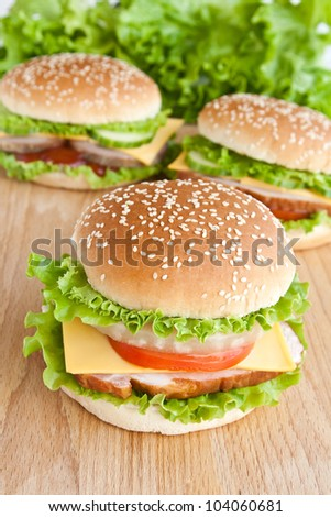 three hamburger with meat and vegetables on wood plate
