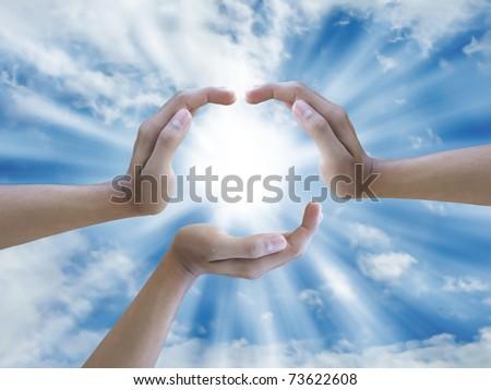 three hand holding the sun