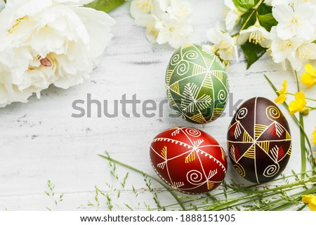 Three handmade Easter eggs decorated with wax-resist dyeing technique. Ukrainian pysanka on white shabby wooden background with empty space for text Photo stock ©