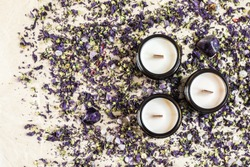 Three handmade ecological soya candle on dry purple flowers  and amethysts with space for text. Wooden wick. Topview