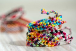 Three handmade homemade colorful natural woven bracelets of friendship isolated on light wooden background, rainbow bright colors, beautiful accessories, chequered design