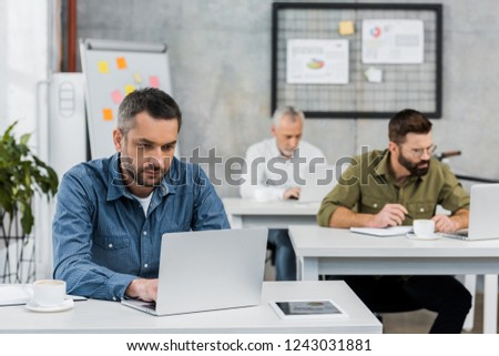 three handsome businessmen working at laptops in office #1243031881