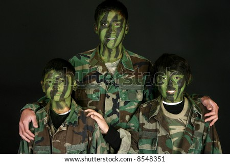 Three handsome Filipino brothers in camo paint and fatigues over black.