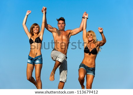 Three handsome young friends holding hands jumping.