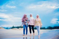 Three happy Arabian woman friends laughing together near the beach  wearing abaya and hijab