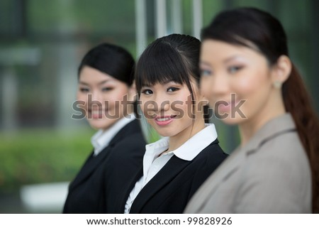 Three happy Asian business women standing in row.