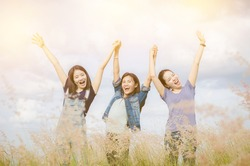 Three happy asian girls smiling and staying in raised hands at grass field with vintage filter, Happiness and togetherness concept.