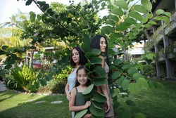 three happy Asian women - a mother and two sisters on vacation on the exotic island of Bali in Indonesia, smiling and hugging