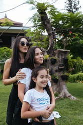 three happy Asian women - a mother and two sisters on vacation on the exotic island of Bali in Indonesia, smiling and hugging, in black and white clothes