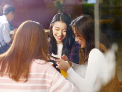 three happy beautiful young asian women sitting at table chatting talking playing with cellphone in coffee shop or tea house, shot through window glass.