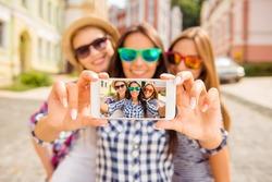 Three happy best girlfriends in glasses making selfie on smartphone.