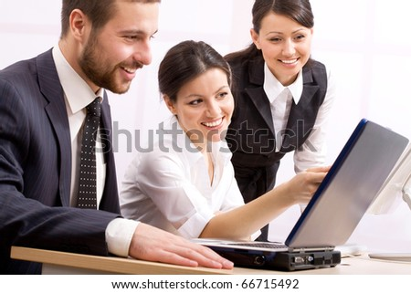 Three happy business people in a meeting at office